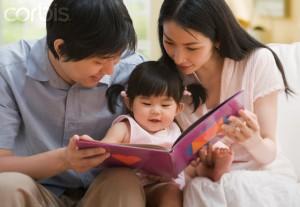 Asian parents reading to baby daughter --- Image by © Jose Luis Pelaez, Inc./Blend Images/Corbis