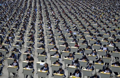 Students take an examination on an open-air playground at a high school in Yichuan, Shaanxi province April 11, 2015. More than 1,700 freshmen students took part in the exam on Saturday, which was the first attempt by the school to take it in open-air. The school said the reasons was due to the insufficient indoor space and also that it could be a test of the students' organizing capacity, local media reported. Picture taken April 11, 2015. REUTERS/Stringer      TPX IMAGES OF THE DAY